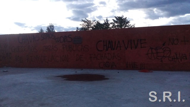 "Graffiti left by Chava, ""We want public works, not remodeling of façades,"" framed by other slogans painted after his murder."